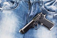 在蓝色牛仔裤的光滑的金属银手枪 免版税库存图片