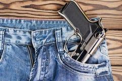 在蓝色牛仔裤的前面口袋的光滑的金属银手枪在老土气木板条的 免版税库存图片