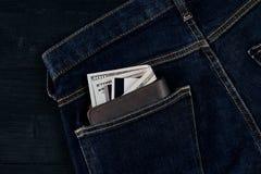 在蓝色牛仔裤的口袋的金钱在木背景的与拷贝空间 库存照片