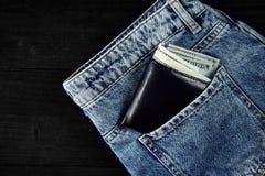 在蓝色牛仔裤的口袋的金钱在木背景的与拷贝空间 库存图片