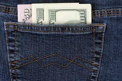 在蓝色牛仔裤的口袋的金钱 免版税库存照片