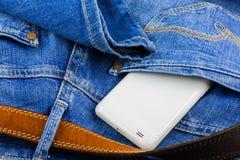 在蓝色牛仔裤的回到矿穴的移动电话 库存图片