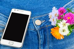 在蓝色牛仔裤的矿穴的移动电话与花的 免版税图库摄影