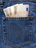 在蓝色牛仔裤的零用钱 免版税库存照片