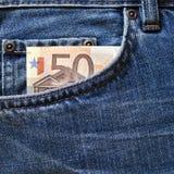 在蓝色牛仔裤的零用钱 免版税库存图片