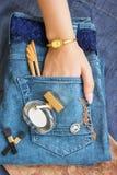 在蓝色牛仔裤谎言香水瓶,金金银细丝工的工作时钟, 库存图片