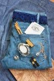 在蓝色牛仔裤谎言香水瓶,金金银细丝工的工作时钟, 免版税库存照片