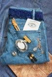 在蓝色牛仔裤谎言香水瓶,金金银细丝工的工作时钟, 免版税库存图片