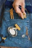 在蓝色牛仔裤谎言香水瓶,金金银细丝工的工作时钟- 库存照片
