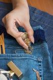 在蓝色牛仔裤谎言香水瓶,金金银细丝工的工作时钟- 库存图片