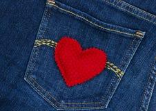 在蓝色牛仔布斜纹布口袋的红色心脏 图库摄影