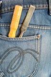 在蓝色牛仔裤口袋的凿子 库存图片