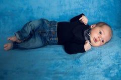 在蓝色牛仔裤和一条黑围巾的新出生的婴孩 库存照片