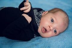 在蓝色牛仔裤和一条黑围巾的新出生的婴孩 库存图片