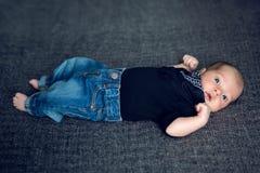在蓝色牛仔裤和一条黑围巾的新出生的婴孩 免版税库存照片