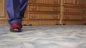 在蓝色牛仔裤和棕色鞋子的人腿做步 股票录像