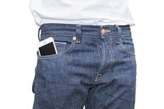 在蓝色牛仔裤牛仔布的口袋的电话 图库摄影