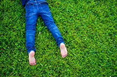 在蓝色牛仔裤的儿童的赤脚 库存照片