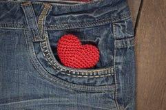在蓝色牛仔裤的前面口袋的一点编织心脏 库存照片
