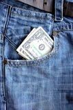 在蓝色牛仔裤的口袋的美国美元 库存图片