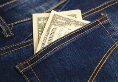 在蓝色牛仔裤的口袋的金钱 免版税库存图片
