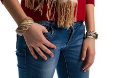 在蓝色牛仔裤的女孩的手 免版税库存照片