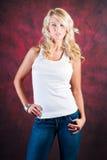 在蓝色牛仔裤的性感的白肤金发的女孩时装模特儿 库存照片