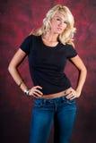 在蓝色牛仔裤的性感的白肤金发的女孩时装模特儿 库存图片