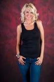 在蓝色牛仔裤的性感的白肤金发的女孩时装模特儿 图库摄影