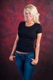 在蓝色牛仔裤的性感的白肤金发的女孩时装模特儿 免版税图库摄影