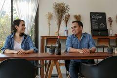 在蓝色牛仔裤的愉快的亚洲夫妇在咖啡店穿戴 免版税库存图片