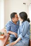 在蓝色牛仔裤的愉快的亚洲夫妇在咖啡店穿戴 免版税图库摄影