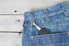 在蓝色牛仔裤的汽车钥匙支持口袋 库存图片
