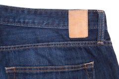 在蓝色牛仔裤的皮革标签 库存照片