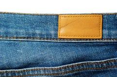 在蓝色牛仔裤的空白的皮革标签在白色 库存照片