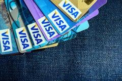 在蓝色牛仔裤的许多签证信用卡 库存图片