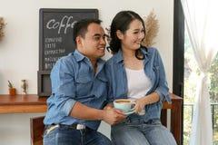 在蓝色牛仔裤礼服的愉快的亚洲夫妇食用热的早晨咖啡 库存照片