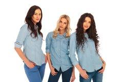 在蓝色牛仔裤衣裳的三个时装模特儿 库存照片