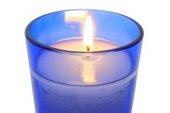 在蓝色玻璃关闭的升蜡烛 库存图片