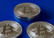 在蓝色玻璃的银色Bitcoins隐藏货币 免版税库存照片