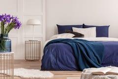 在蓝色玻璃花瓶的紫色花在时髦的桌上在白色卧室内部与舒适的床 免版税库存图片