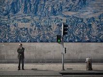 在蓝色瓦片墙壁前面的人 库存照片