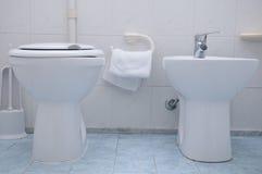 在蓝色瓦片的净身盆和洗手间白色 免版税库存图片