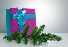 在蓝色的一个美丽的礼物盒,与一把紫色丝带和弓 在她前是圣诞树的分支 一异常 免版税库存图片
