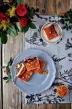 在蓝色的一张木桌上板材是凝乳蛋糕用海鼠李 用花和一个分支装饰与臀部 从abov的看法 库存图片