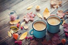 在蓝色的咖啡上釉了杯子和秋叶 免版税图库摄影