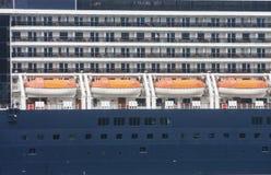 在蓝色的四艘橙色救生艇 免版税库存照片