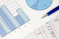 在蓝色的图形与电子表格和笔 免版税库存图片