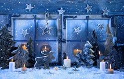 在蓝色的室外圣诞节窗口装饰与木头和蜡烛 库存图片