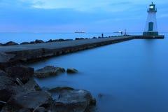 在蓝色的岩石灯塔和码头 图库摄影